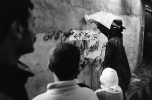 Hamas-lid verwijdert de tekst 'Wij zijn trots op Naafi Sjam'. De PLO spoot deze tekst op het huis van Naafi Sjam nadat hij door het Israëlische leger was doodgeschoten, Beach Camp, Gaza, 1993