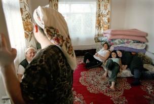 Kamer: drie vrouwen zitten bij stapel dekens; links staan nog twee vrouwen, Nederland, 2004