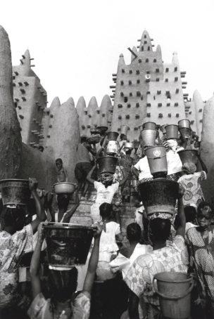 Meisjes dragen in emmers water naar de Moskee van Djenné, Mali, 2000