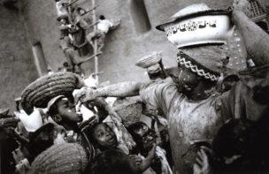 Ter aanmoediging worden er tijdens de crépissage 'poffertjes' uitgedeeld aan de hardwerkende kinderen. Veel mensen uit de stad bieden iets aan om uit te delen, Djenné, Mali, 2000